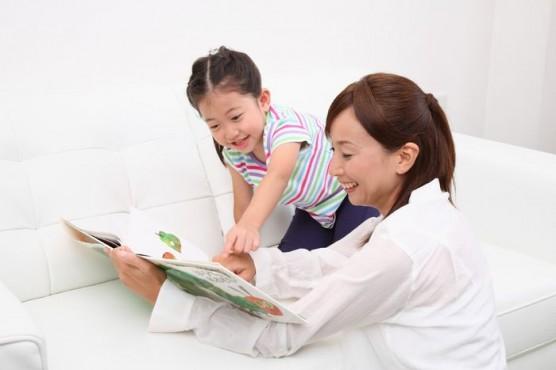 絵本の読み聞かせをする家族 (1)